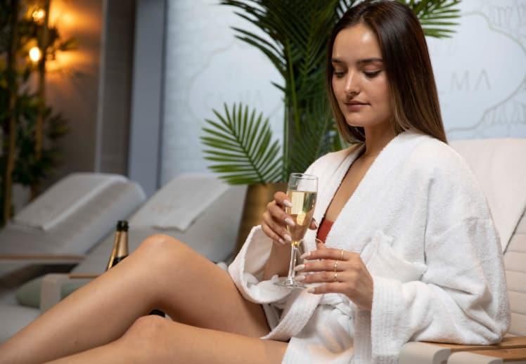 בחורה בחלוק מגבת לבן אוחזת בכוס שמפניה